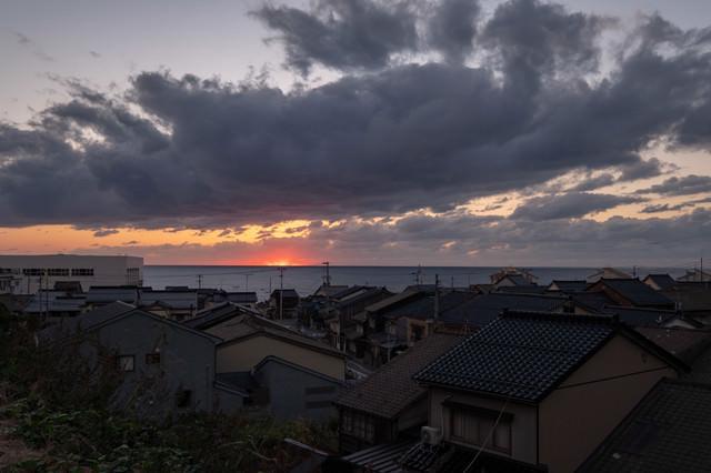 沈む夕日と海沿いの民家の写真