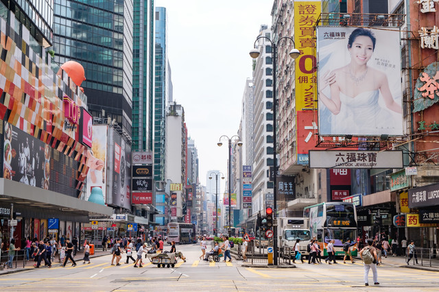 香港の都市部の景観と横断する人々の写真