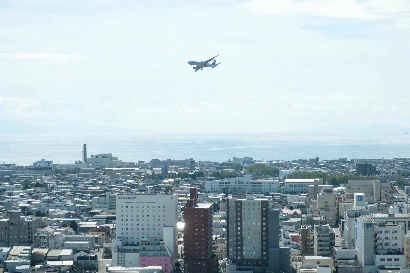 「街の上空を飛ぶ旅客機」の写真