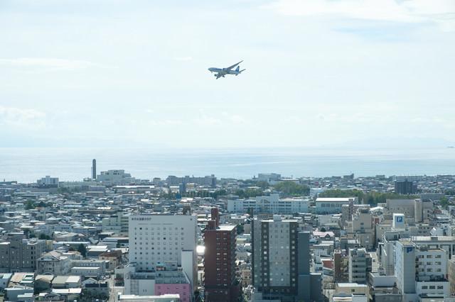 街の上空を飛ぶ旅客機の写真