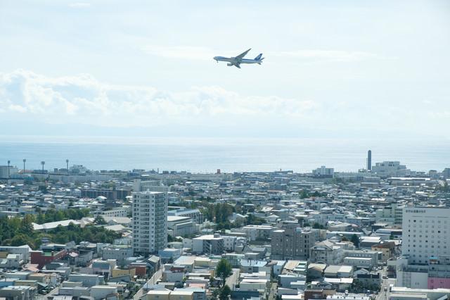 街並みと離陸した旅客機(函館空港)の写真