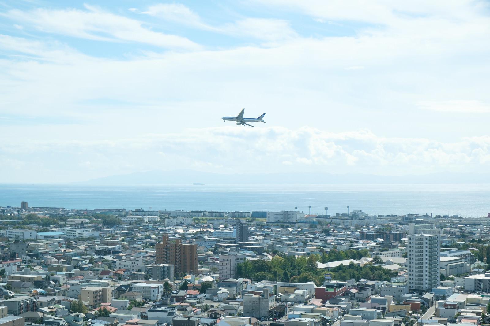 「市街地の上空を旋回する旅客機」の写真