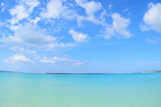 沖縄の海と遠くに見える防波堤の写真