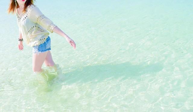 穏やかな透明な海の浅瀬を歩く女性