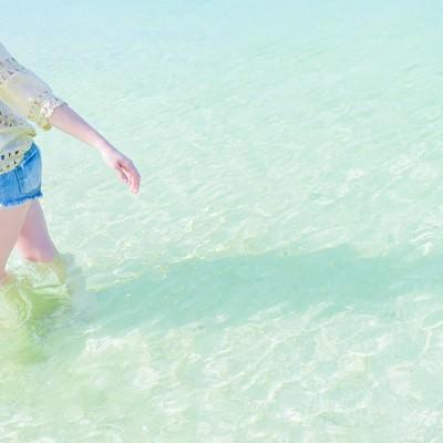 穏やかな透明な海の浅瀬を歩く女性の写真