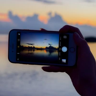「スマホで夕暮れ時の海を撮影」の写真素材