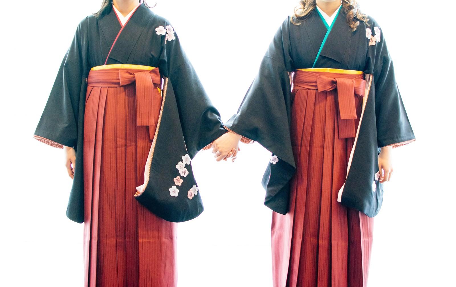 「手を繋いで卒業を迎える袴姿の女子」の写真