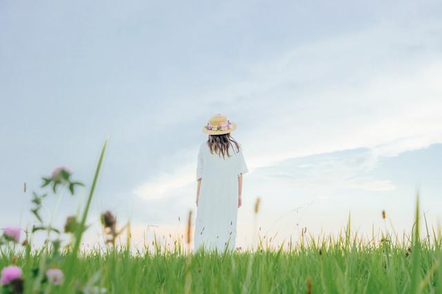 草原で立ちつくす麦わら帽子の女性の写真