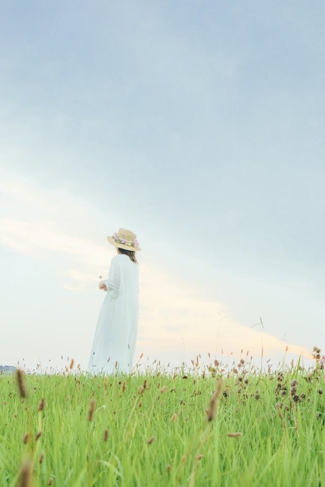 草原で遠くを見つめる女性の後ろ姿の写真