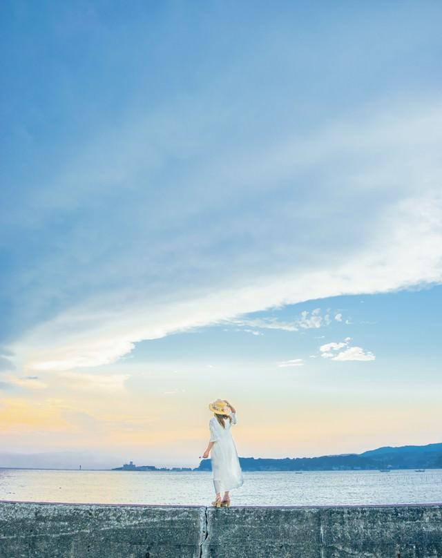 堤防に立ち海を見ている麦わら帽子の女性の写真