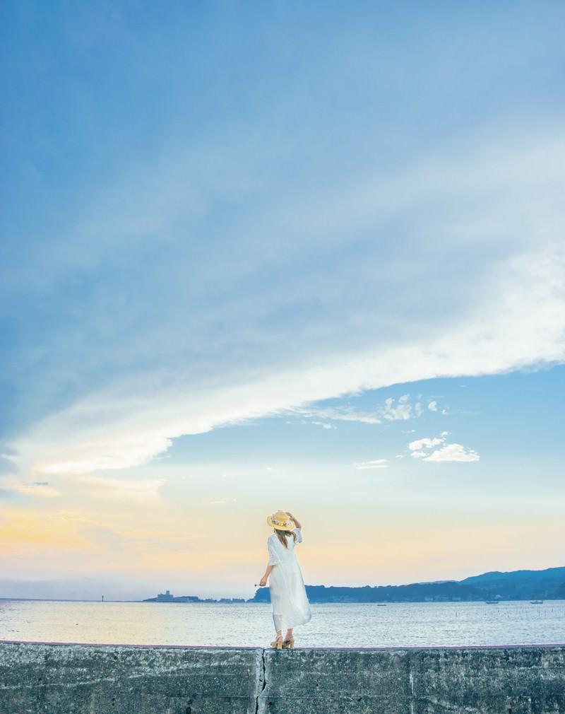 「堤防に立ち海を見ている麦わら帽子の女性」の写真