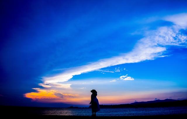 トワイライトの海岸を歩く帽子をかぶった女性のシルエットの写真
