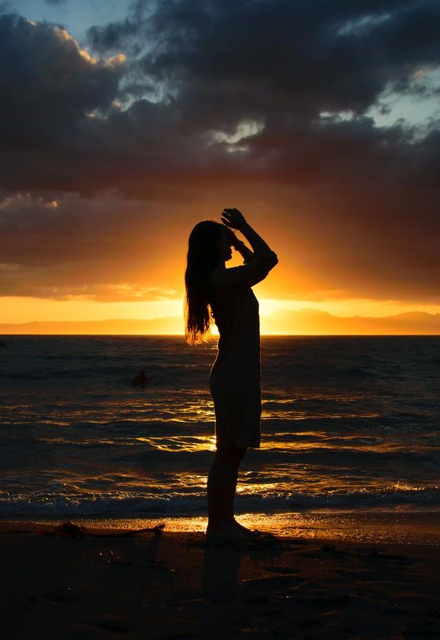 夕日をバックに砂浜で髪をかきあげようとする女性のシルエットの写真