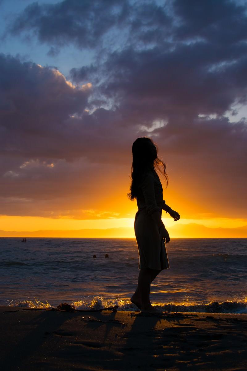 「夕日に照らされる砂浜を歩く女性のシルエット」の写真