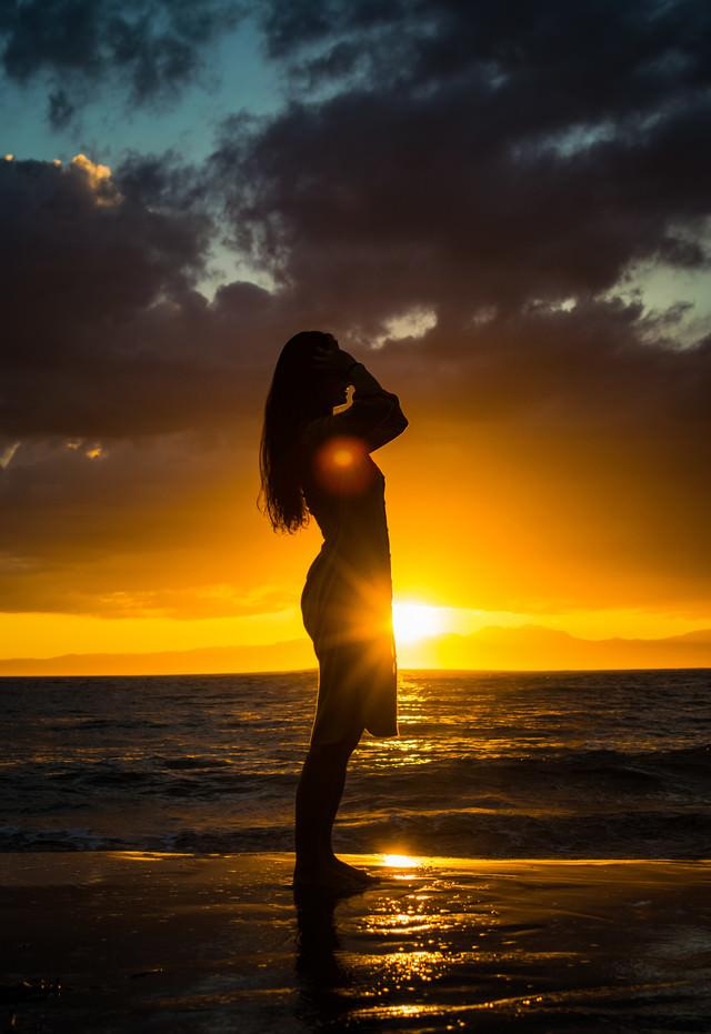 夕日のレイラインに立つ女性のシルエットの写真