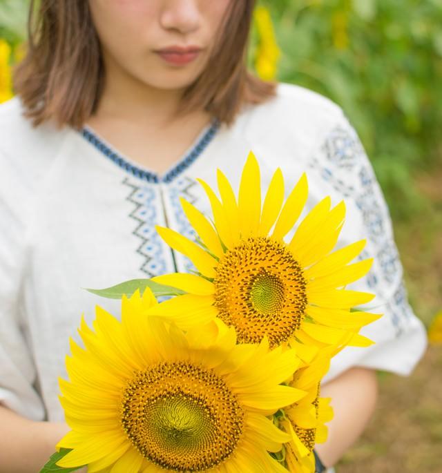 向日葵の花を抱えた女性の写真