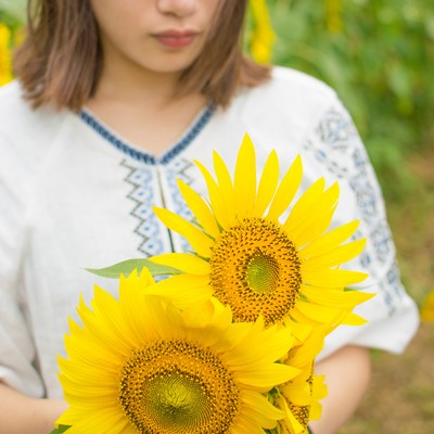 「向日葵の花を抱えた女性」の写真素材