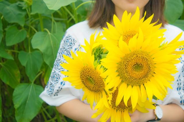 向日葵の花を持った女性の写真