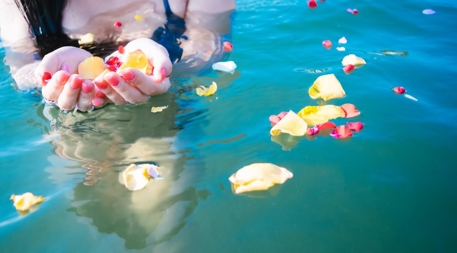 「水面に浮く鮮やかな花びらと女性の手水面に浮く鮮やかな花びらと女性の手」のフリー写真素材を拡大