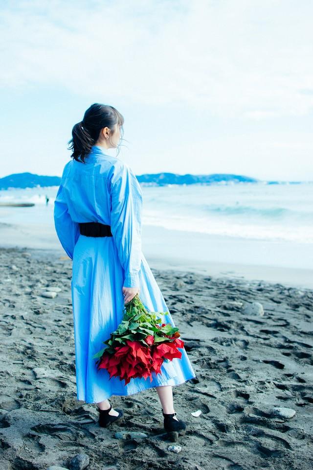 波打ち際で赤い花束を手にする女性の写真