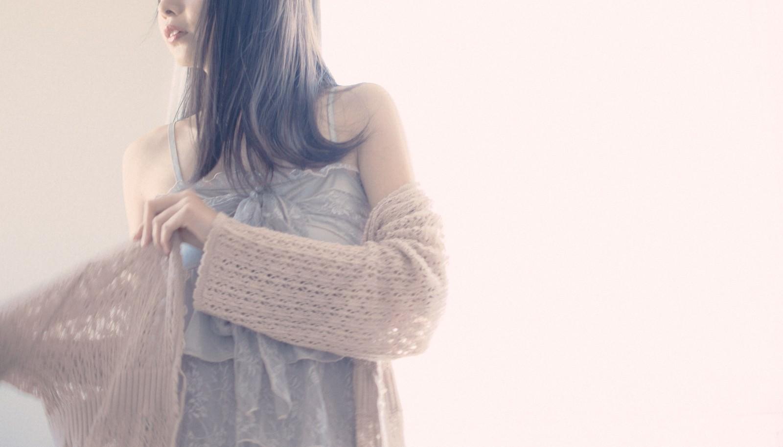 「薄手のトッパーカーディガンに袖を通す女性」の写真