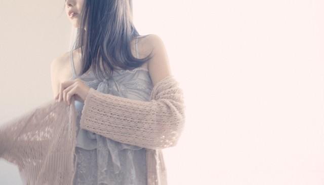 薄手のトッパーカーディガンに袖を通す女性の写真