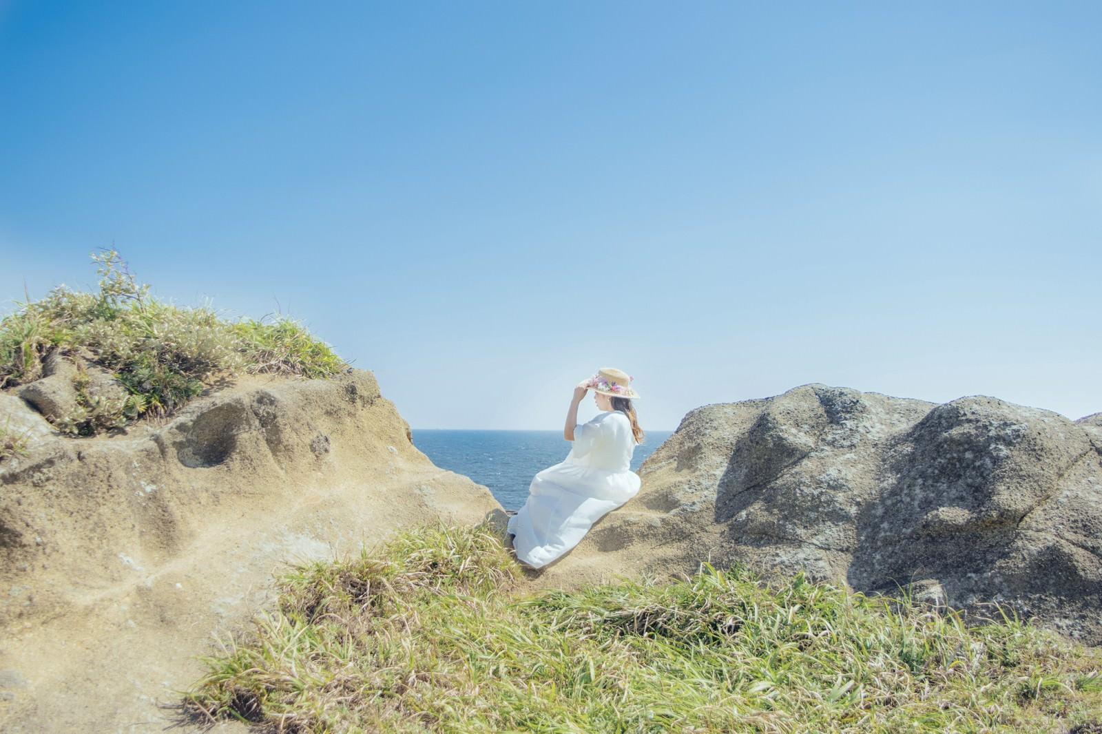 「海岸に腰を下ろし海を見つめる女性」の写真