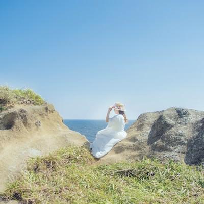 海岸に腰を下ろし海を見つめる女性の写真