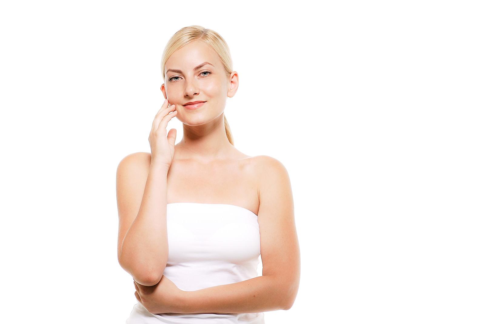 「右頬に指を添えてこちらを見る金髪モデルの女性」の写真[モデル:モデルファクトリー]