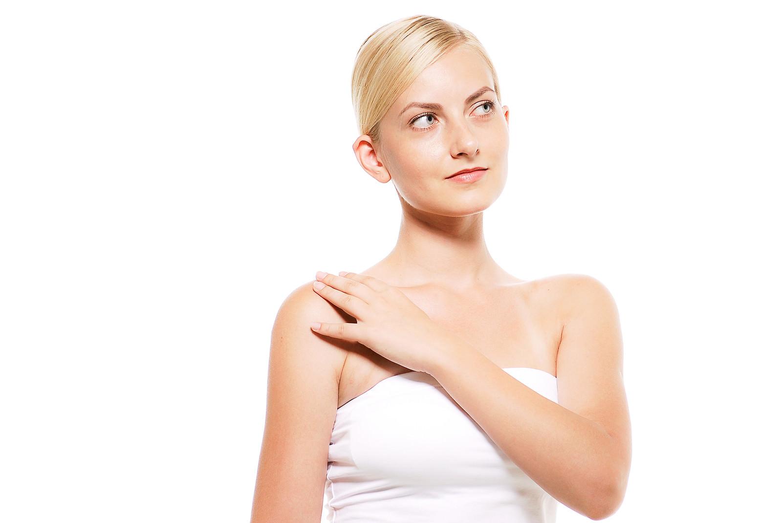「右肩の張りを確認している外国人の女性」の写真[モデル:モデルファクトリー]
