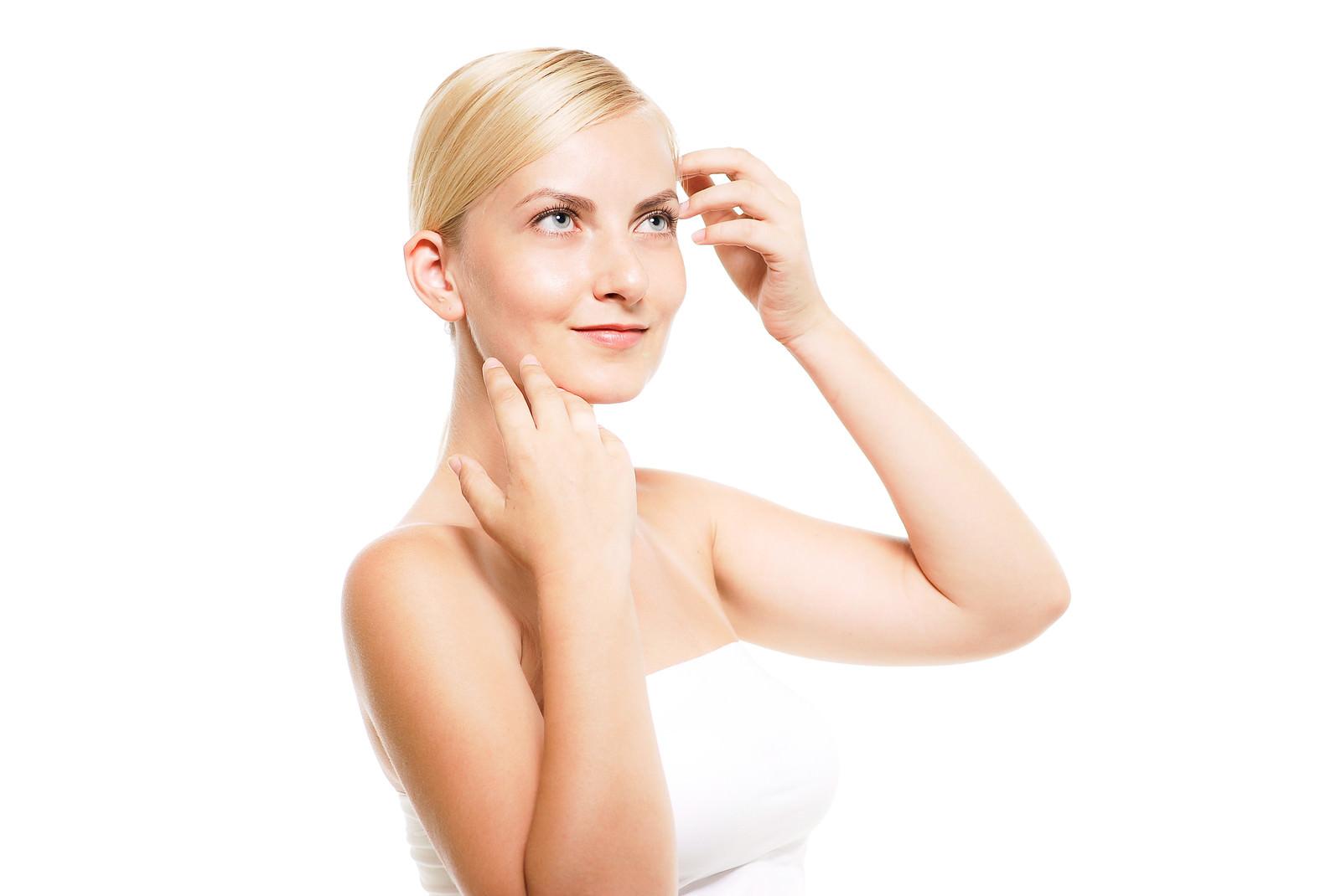 「軽く見上げながら肌の調子を整える外国人の女性」の写真[モデル:モデルファクトリー]