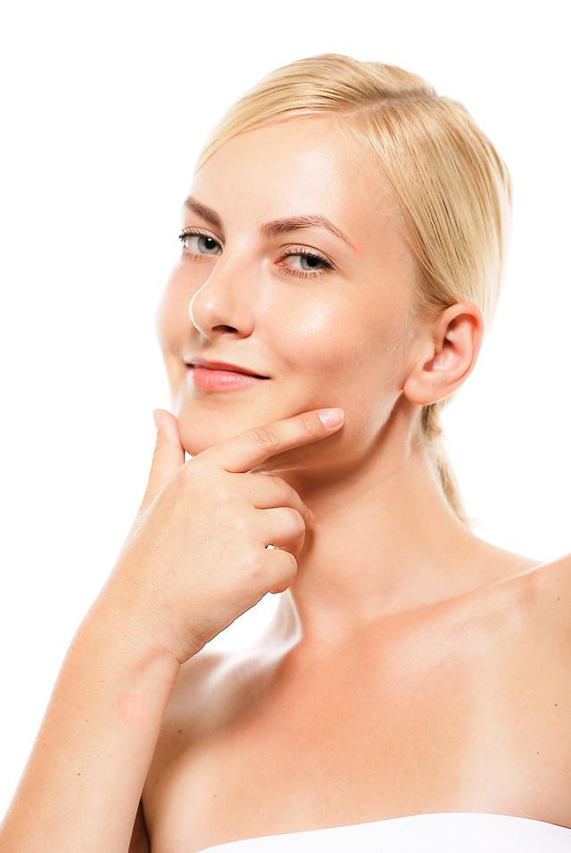 顎に手を当てる外国人美容女性の写真