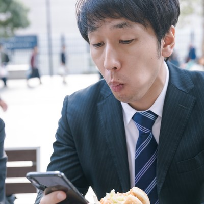 ファーストフードを食べながらスマホをチェックする現代サラリーマンの写真