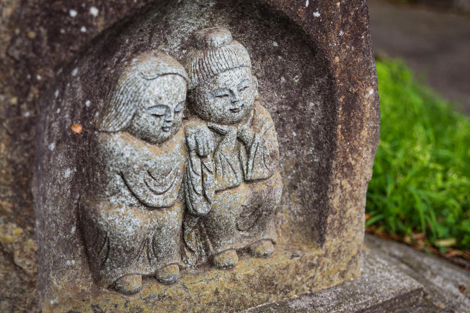 「寄り添う姿の「双体道祖神」の石像」の写真
