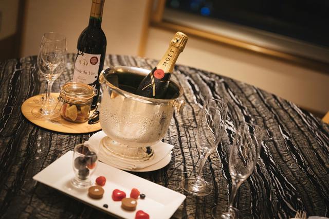 テーブル上に置かれたシャンパンとワインの写真
