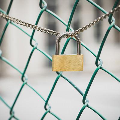 南京錠とフェンスの写真