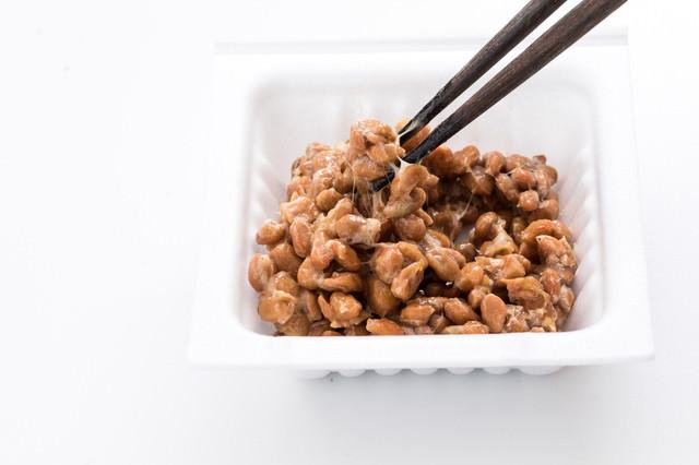 パックに入った納豆をかき混ぜるの写真