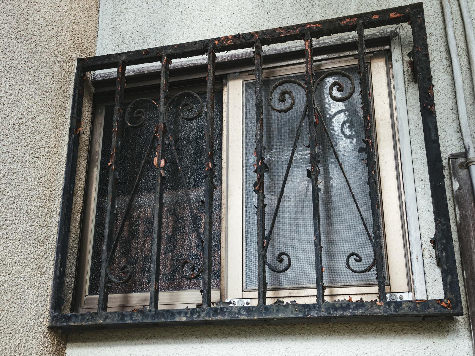 「錆びて塗装が剥げた格子(廃屋)」の写真