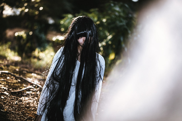 呆然と立ちすくむ不気味な髪の長い女性の写真