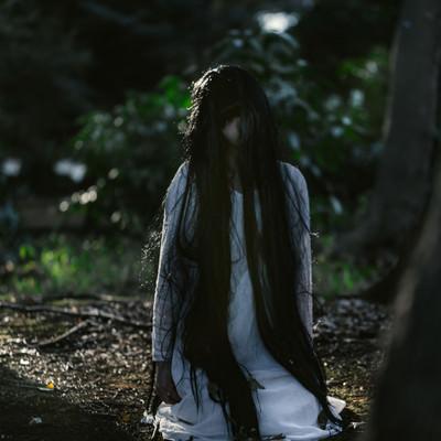 「樹海で座り込む未練を残した女性」の写真素材