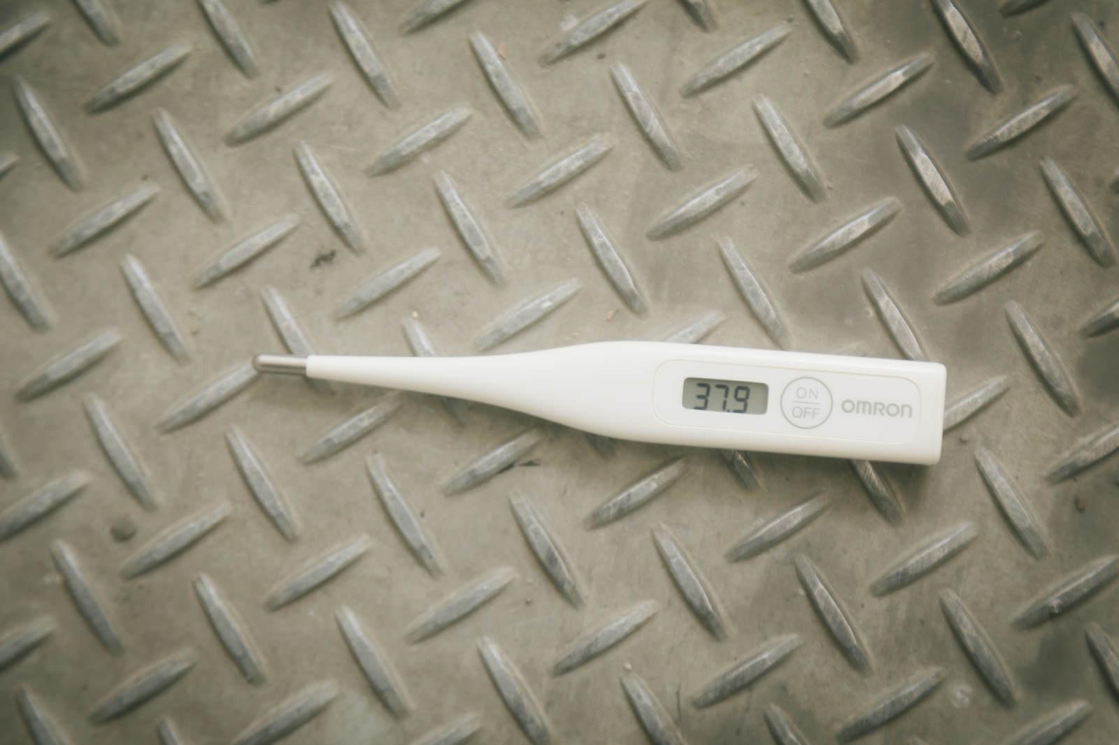 「足場板に置かれた体温計(37.9度)」の写真