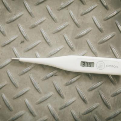 足場板に置かれた体温計(37.9度)の写真