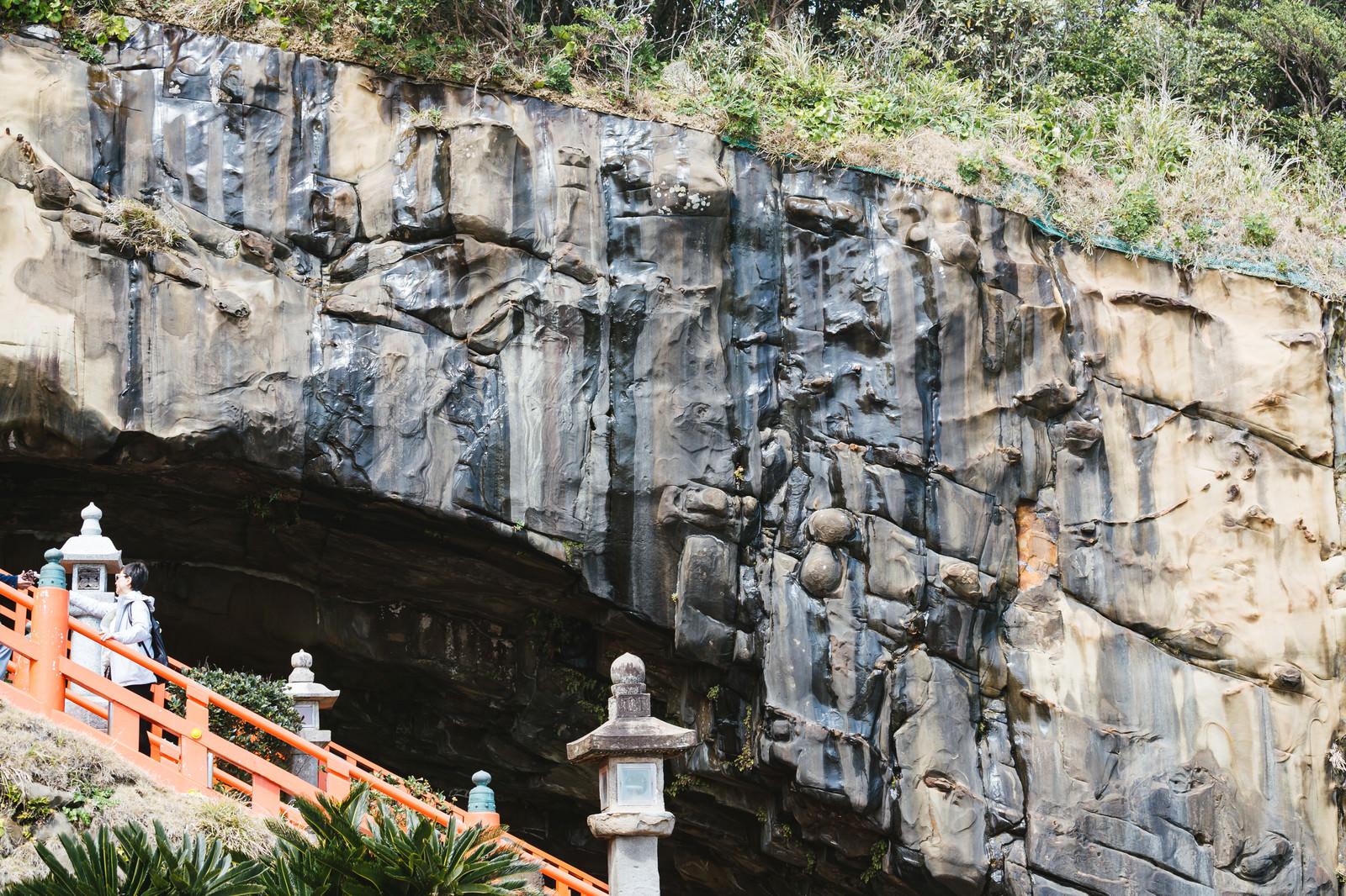 「どこかに顔が隠れてる鵜戸神宮神殿を覆う岩壁と滴る湧き水」の写真