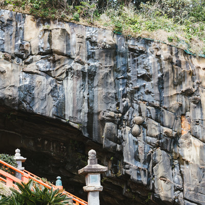 どこかに顔が隠れてる鵜戸神宮神殿を覆う岩壁と滴る湧き水の写真