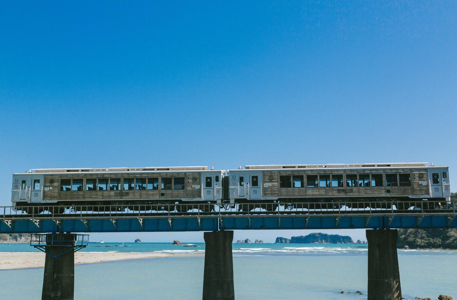 「七ツ八重をバックに走る観光列車「海幸山幸」」の写真