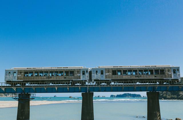 七ツ八重をバックに走る観光列車「海幸山幸」の写真