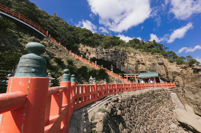 断崖にある鵜戸神宮と朱塗りの柵(玉垣)の写真