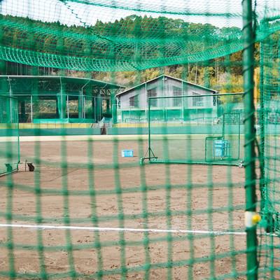 「野球場で練習中(ネット越し)」の写真素材