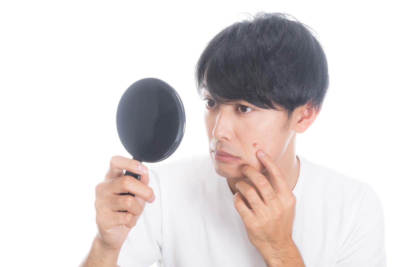 「手鏡でニキビを確認する男性」の写真[モデル:完伍]