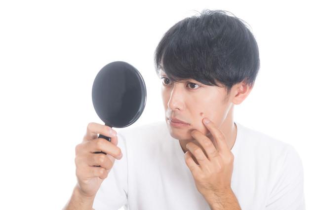 手鏡でニキビを確認する男性の写真